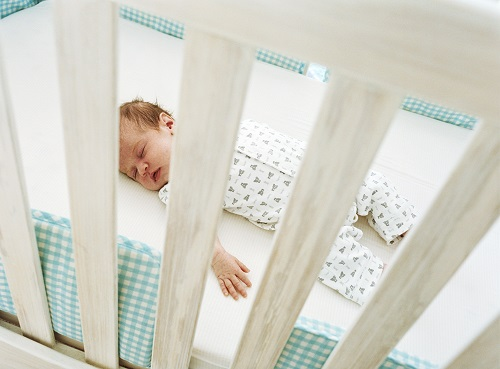 Baby sleeping in baby cot