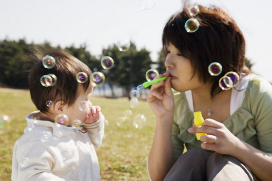 mother blowing bubble and playing with baby